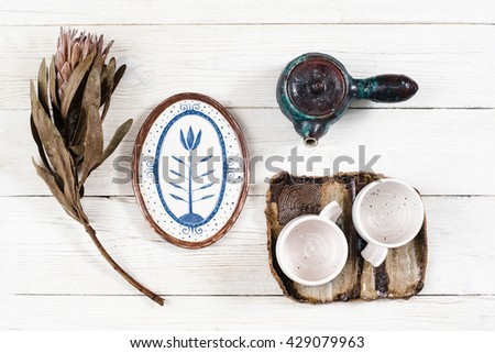 Flat lay of rustic clay dishes for tea. Tea utensil composition with flower on white wooden background. Teapot, two cups on saucer, plate and flower on white table closeup - stock photo