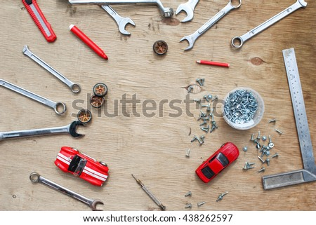 Flat lay of set of tools for car repairing on wooden background with contrast red toy cars. Top view. - stock photo