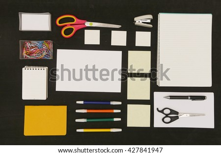 Flat lay photo of office desk with papers and lots of stationery objects - stock photo