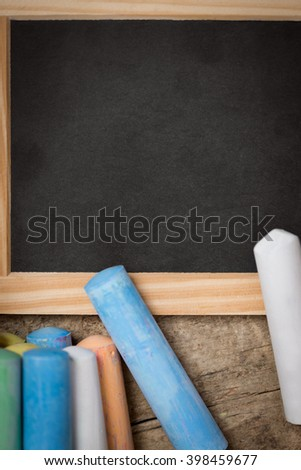 Flat lay, slate with colorful crayon, copyspace for text - stock photo