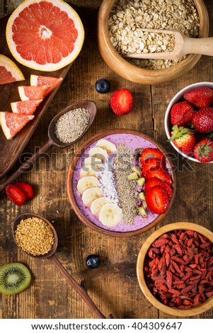 Flat lay super food. Acai berry smoothie bowl topped with chia seeds, coconut flakes, banana, strawberries and kiwi with variety of superfoods on rustic wooden table. Above view - stock photo