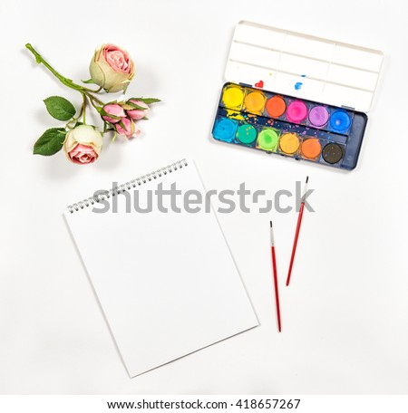 Flat lay with sketchbook, watercolor, brushes, paper, rose flowers on white background - stock photo