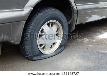 Flat rear tire on car - stock photo