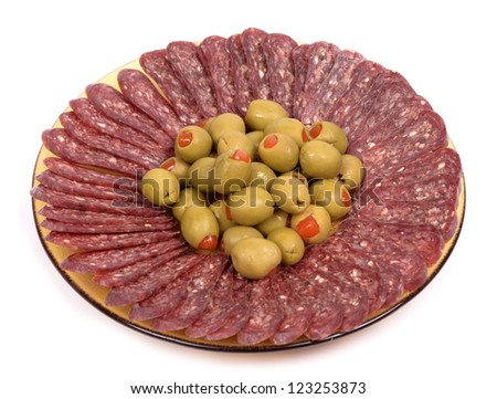 flat sausage in plate garnished with olives on a white background - stock photo