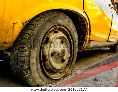 Flat tire of an old yellow car with rusted rim. - stock photo
