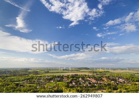 Flat west German landscape near Aachen and Herzogenrath with lots of wind turbines and some clouds on blue sky. - stock photo