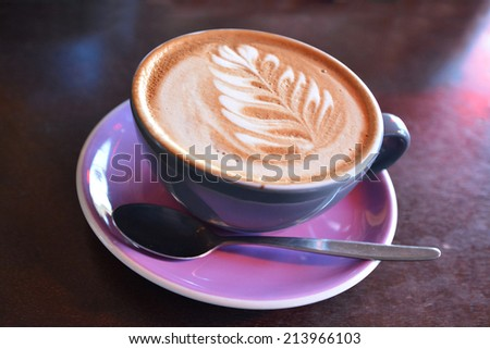Flat white coffee decorated with the New Zealand iconic symbol the silver fern on it. Copy space - stock photo