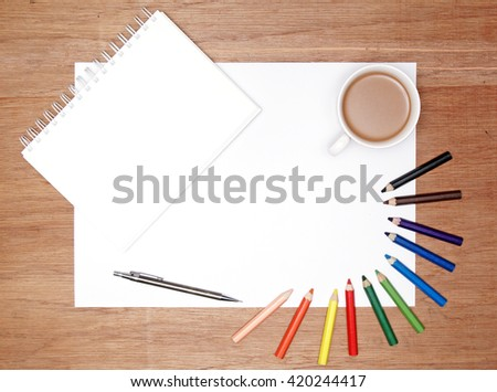flatlay of white drawing paper, cup of coffee, colouring pencils, and a spiral bound book.  - stock photo