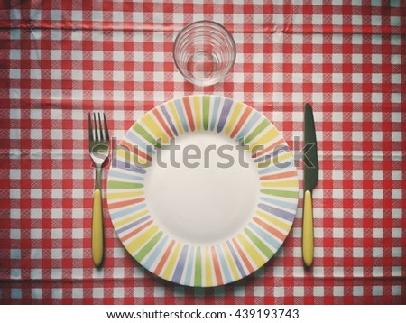 Flatware and squared tablecloth on a table before lunch vintage filtered image - stock photo
