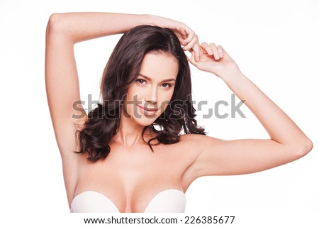 Flaunting her femininity. Portrait of beautiful young woman looking at camera and holding hands upon her head while standing against white background   - stock photo