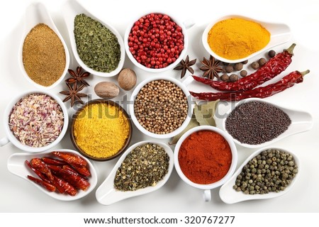 Flavorful, colorful spices in ceramic and metal bowls on white background. - stock photo
