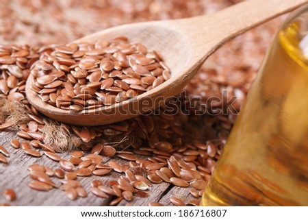 Flax seed in a wooden spoon and a bottle with oil. macro horizontal  - stock photo
