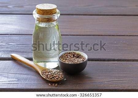flax seed oil in glass bottle on a wooden table - stock photo