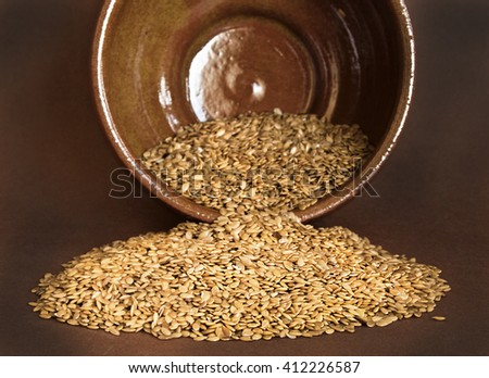 Flax seed on ceramic bowl on brown background - stock photo