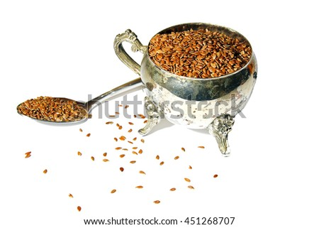 Flax seeds in a metal container on white background. - stock photo