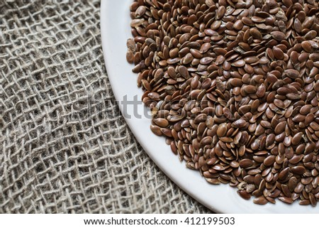 Flax seeds in a plate on a linen cloth, raw material, cloth bags, linen yarn, grunge texture, linen filament, linen fiber, the ingredients for a healthy diet, flaxseed, plants' seeds   - stock photo