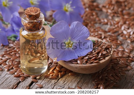 flax seeds in a spoon and oil in a bottle on the table close-up horizontal  - stock photo