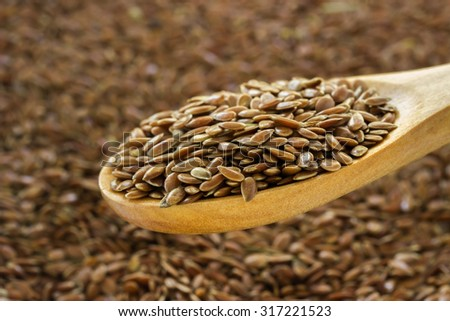 Flax seeds in a spoon on a blurred  background closeup. - stock photo