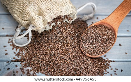 Flax seeds in a wood spoon on a wooden background. Linseed is scattered from a linen bag. - stock photo