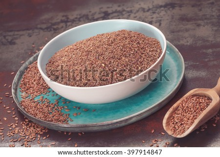 Flax seeds in bowl. Whole and ground flax seed  in ceramic dishes and wooden spoon.  Macro, selective focus, vintage toned image - stock photo