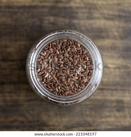 flax seeds in glass jar on wooden table, from  above - stock photo