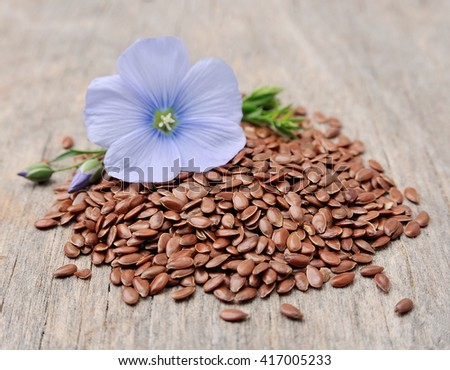 Flax seeds with flowers close up on wooden texture - stock photo