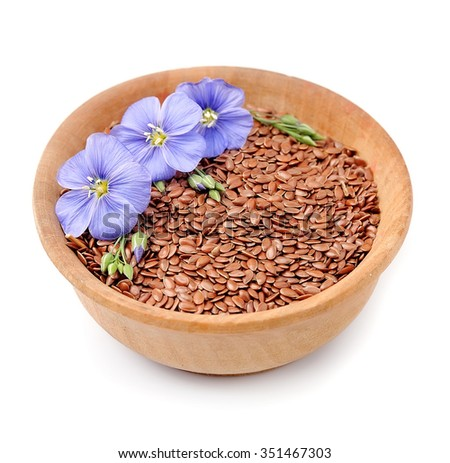 Flax seeds with flowers on the plate isolated. - stock photo