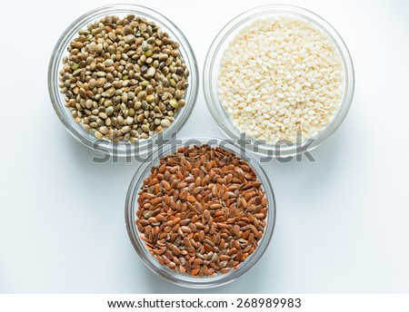 Flax, sesame, and hemp seeds in glass bowls - stock photo