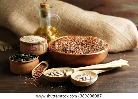 Flax, sesame, pumpkin and sunflower seeds with oil on wooden table background, closeup - stock photo