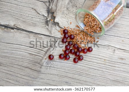 Flaxseed oil in capsules on a fray wooden surface. - stock photo