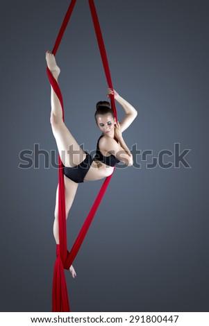 Flexible female gymnast performing aerial exercise - stock photo