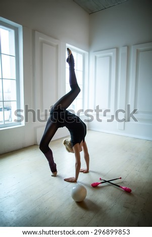 Flexible gymnast doing exercise - stock photo