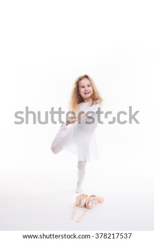 Flexible little girl ballerina doing gymnastic exercises on white background. - stock photo