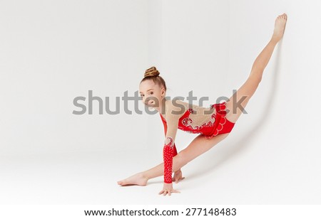 Flexible little girl in red dress doing gymnastic exercises on white background - stock photo