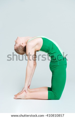 Flexible woman doing yoga exercise isolated on a white background - stock photo
