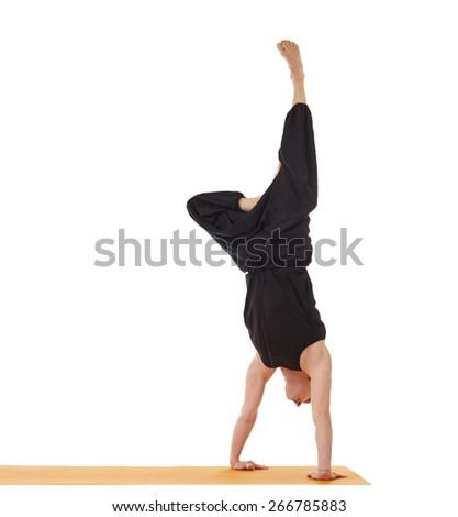 Flexible yoga man doing handstand in studio - stock photo