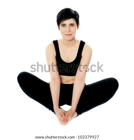 Flexible yoga woman holding her legs. Isolated in studio - stock photo