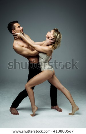Flexible young modern acrobats couple posing in studio. Fashion portrait of attractive dancing couple. Man and woman. Passion. Love. perfect skin facial and make-up, blonde hair. The guy's pumped abs. - stock photo
