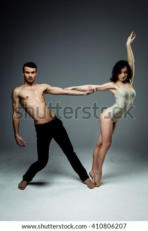 Flexible young modern acrobats couple posing in studio. Fashion portrait of attractive dancing couple. Man and woman. Passion. Love. perfect skin facial and make-up, brunet hair. The guy's pumped abs. - stock photo