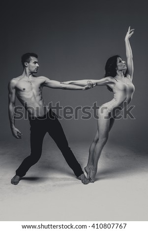 Flexible young modern acrobats couple posing in studio. Fashion portrait of attractive dancing couple. Man and woman. Passion. Love. perfect skin facial and make-up. black and white photo - stock photo