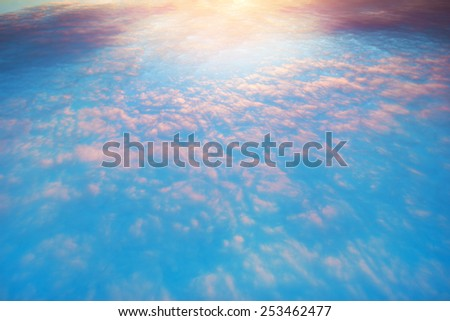 Flight above the colorful clouds. - stock photo