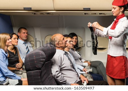Flight attendant safety demo fastening seat belt passenger airplane cabin - stock photo