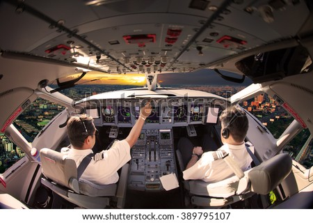 Flight Deck of modern aircraft. Pilots at work. Sunset view from the plane cockpit. - stock photo