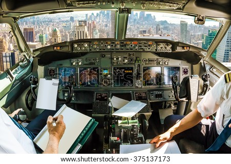 Flight in airplane cabin interior on New York skyline of United States of America.. Pilots arms and blank white papers for copy space - stock photo