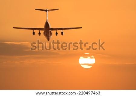 Flight of the cargo plane on the sunset background. - stock photo