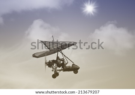 Flight of the motor deltaplane above the clouds. Vintage image. - stock photo