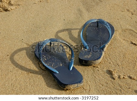 Flip-flop sandals left at the beach - stock photo