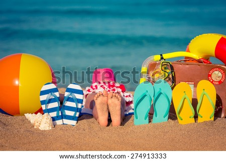 Flip-flops and children feet on the beach. Summer vacation concept - stock photo