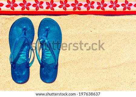 Flip flops and towel at the beach.  - stock photo