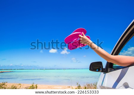 Flip Flops from the window of a car on background tropical beach - stock photo